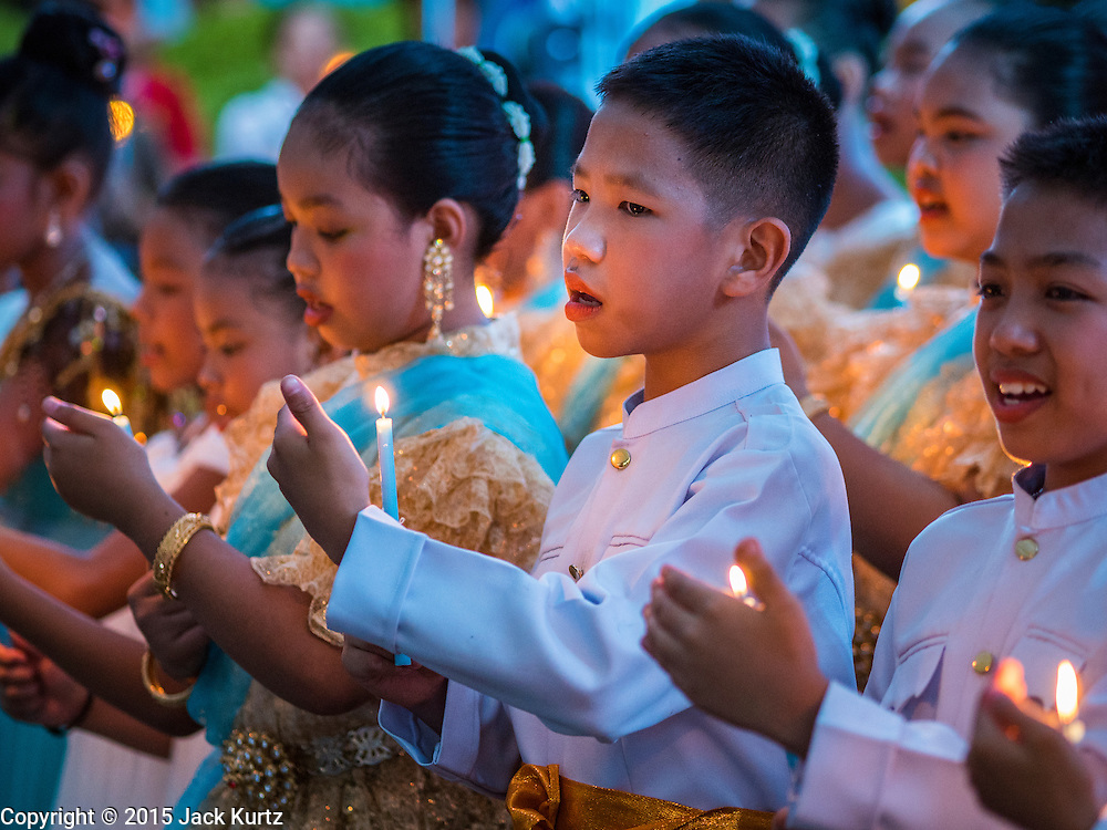 12 AUGUST 2015 - BANGKOK, THAILAND:  Thai students lead people in singing the Queen's Anthem during a celebration for Queen Sirikit of Thailand on her 83rd birthday. Queen Sirikit was born Mom Rajawongse Sirikit Kitiyakara on August 12, 1932. She is the queen consort of Bhumibol Adulyadej, King (Rama IX) of Thailand. She met Bhumibol in Paris, where her father was the Thai ambassador. They married in 1950, she was appointed Queen Regent in 1956. The King and Queen had one son and three daughters. She has not made any public appearances since her hospitalization in 2012. Her birthday is celebrated as Mother's Day in Thailand, schools and temples across Thailand hold ceremonies to honor the Queen and mothers.   PHOTO BY JACK KURTZ