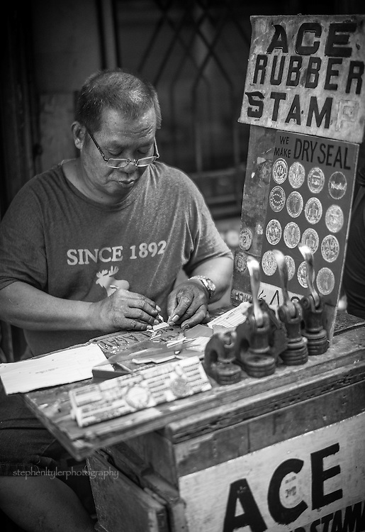 Old school dry seal and stamp maker working on a project on a street corner in the Quiapo section of Metro Manila.
