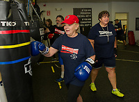 """Carol Sacknoff, Richard Laflamme and Barbara Lewis work the punching bags with their Coach Betty Collins during the """"Rock Steady Boxing"""" class at the Downtown Gym on Thursday.   (Karen Bobotas/for the Laconia Daily Sun)"""