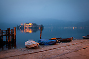 Rowboats docked in Orta San Giulio, with Isola San Giulio in the distance, Piedmont, Italy.