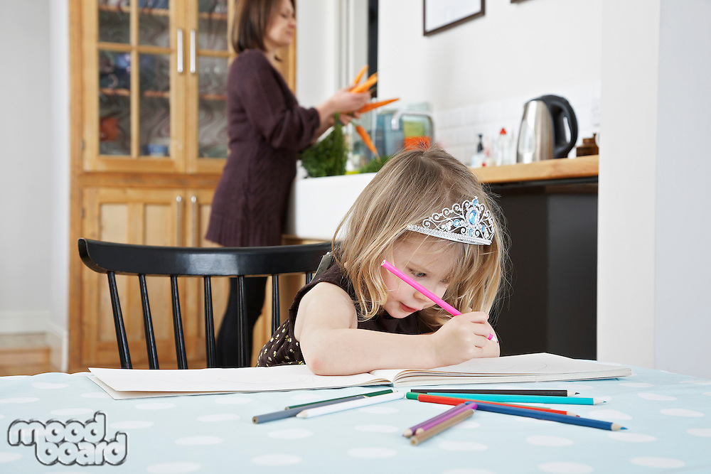 Girl (3-4) drawing in kitchen mother preparing food in background