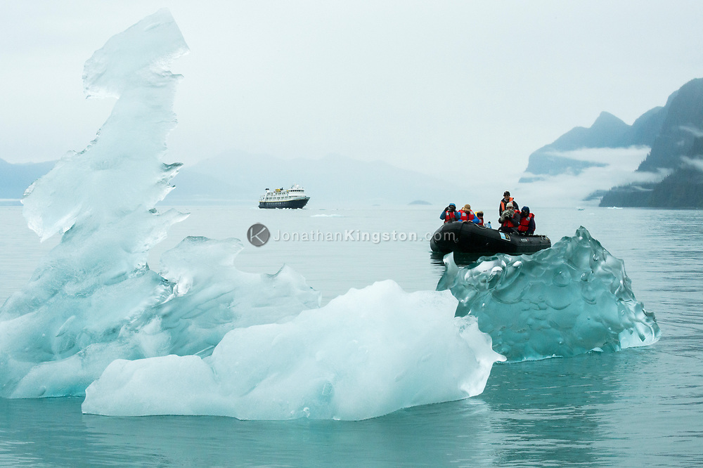Tourists photograph a crystal clear iceberg floating in the ocean in front of a small cruise ship near the LeConte glacier, Petersburg, Alaska.
