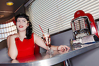 Young beautiful woman in red dress with chocolate smoothie at restaurant table
