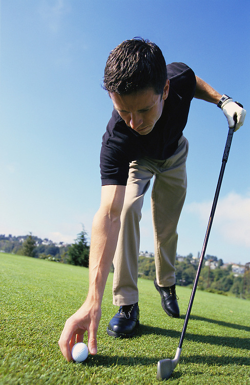 A man bending over to tee up his golf ball<br />