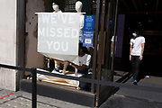 As the UK's Coronavirus lockdown continues to ease, retailers re-open their doors to shoppers, an employee of a Levis shop on Regent Street awaits customers with hand sanitiser dispensers, and another unpeels the sticky stencil lettering telling customers that they've been missed, on 18th June 2020, in London, England.