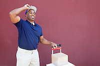 Happy young African American delivery man standing with handtruck over colored background