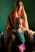 """Shashi Devi (aged 28) sits in her house in the village of Shahpurjat, Ghaziabad, Uttar Pradesh, India. While Shashi had a tubectomy done after having 2 sons, Monika, her brother-in-law's wife, is still trying for a son after having 2 daughters. Shashi did the operation because she wanted to """"give her 2 children the best and inflation will make things difficult"""", and she believes that a """"small family = happy family"""". She has been pushing Monika to get her husband to do an NSV so that Monika's life is not endangered since her previous pregnancies have been complicated. Photo by Suzanne Lee / Panos London"""