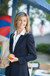 Woman in a business suit holding a paper bag and a mango by a fruit stand