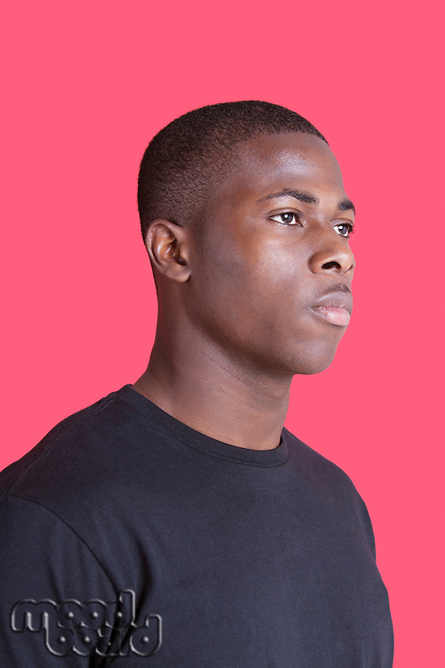 Serious African American young man looking away over pink background