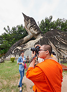 Laos. Vientiane Prefecture. Buddha Park (Wat Xieng Khuan). A Buddhist monk taking a souvenir photo.