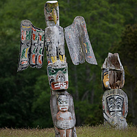 Totem poles at the 'Namgis burial grounds and cemetery in Alert Bay, Cormorant Island, British Columbia, Canada. Pole shown is Eagle, Bear holding Man carved by Charlie James Yakudlas.