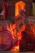 Women worship together at Scindia Ghat along the Ganges River during Diwali, the Festival of Lights, one of the most important Hindu religious festivals, in Varanasi India.