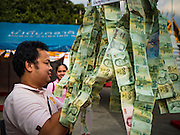 24 NOVEMBER 2015 - BANGKOK, THAILAND: A man staples 20 Baht notes (about .60¢ US) to a chain of donations at the Wat Saket temple fair. Wat Saket is on a man-made hill in the historic section of Bangkok. The temple has golden spire that is 260 feet high which was the highest point in Bangkok for more than 100 years. The temple construction began in the 1800s in the reign of King Rama III and was completed in the reign of King Rama IV. The annual temple fair is held on the 12th lunar month, for nine days around the November full moon. During the fair a red cloth (reminiscent of a monk's robe) is placed around the Golden Mount while the temple grounds hosts Thai traditional theatre, food stalls and traditional shows.       PHOTO BY JACK KURTZ