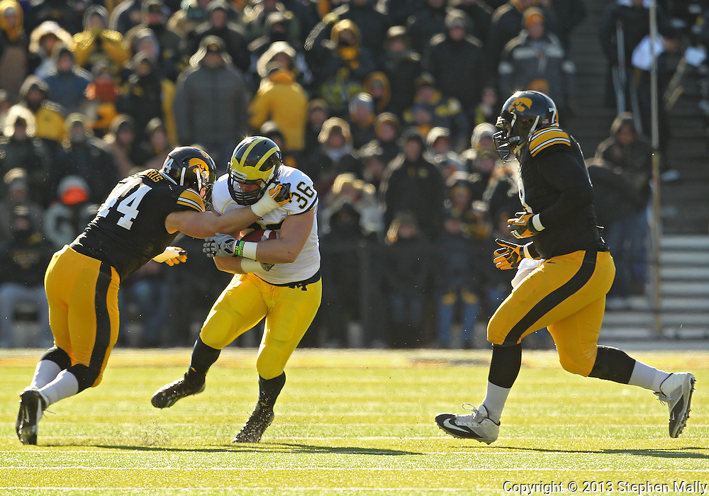 November 23 2013: Michigan Wolverines fullback Joe Kerridge (36) is hit by Iowa Hawkeyes linebacker James Morris (44) on a run during the first quarter of the NCAA football game between the Michigan Wolverines and the Iowa Hawkeyes at Kinnick Stadium in Iowa City, Iowa on November 23, 2013. Iowa defeated Michigan 24-21.