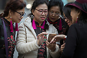 A group of lady tourists from south-east Asia enjoy looking at the screen of a mobile phone, on 15th November 2018, in London, England.