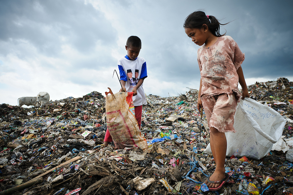 Idris, 13, and Annie, 8, collecting plastic and metal waste on an older section of the 'Trash mountain', Makassar, Sulawesi, Indonesia.
