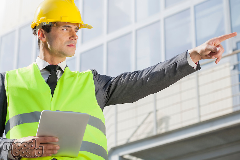 Young male engineer with digital tablet pointing away outside industry