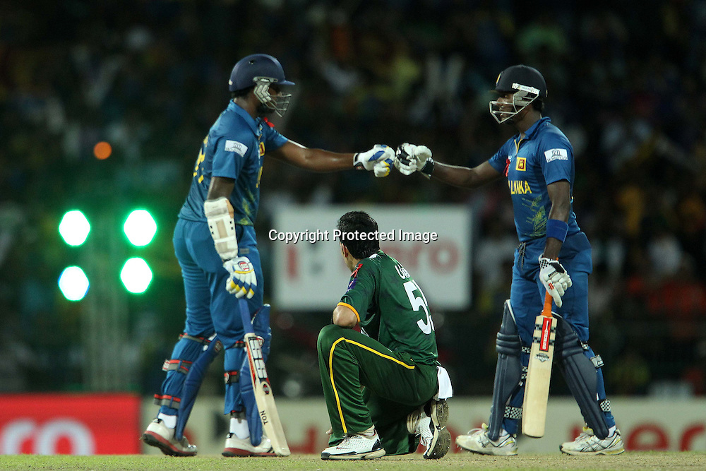 Umar Gul watches as Thisara Perera and Jeewan Mendis congratulate each other on a boundary from his bowling during the ICC World Twenty20 semi final match between Sri Lanka and Pakistan held at the Premadasa Stadium in Colombo, Sri Lanka on the 4th October 2012<br /> <br /> Photo by Ron Gaunt/SPORTZPICS