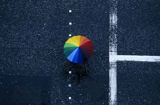 A pedestrian takes cover under a rainbow-colored umbrella while crossing Princes Street during a drizzly day in Edinburgh, Scotland.