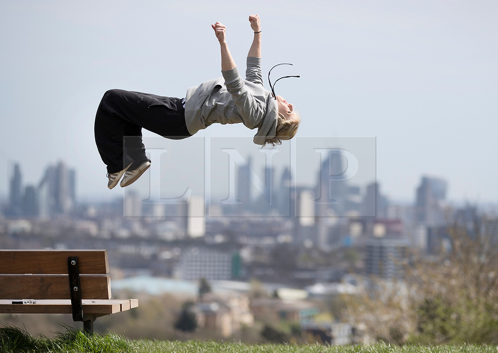 © Licensed to London News Pictures. 17/04/2018. London, UK. A member of the 'No Show' all female acrobatic troupe performs a back flip in sight of the London skyline from Parliament Hill in warm afternoon sunshine. 'No Show' are performing in the Roundhouse's third week of CircusFest with fellow all female troupe 'The Bekkrell Effect'. Photo credit: Peter Macdiarmid/LNP