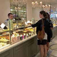 Girls selecting macarons at Laduree Royale.
