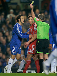 LONDON, ENGLAND - Wednesday, December 19, 2007: Liverpool's Xabi Alonso is shown the yellow card from referee Martin Atkinson with help from Chelsea's Ricardo Carvalho during the League Cup Quarter Final match at Stamford Bridge. (Photo by David Rawcliffe/Propaganda)