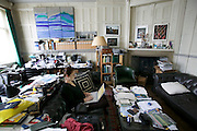 Faith D'Aluisio checking email on her computer in the cluttered home office of Philip Achache on Tite St. in London, UK.