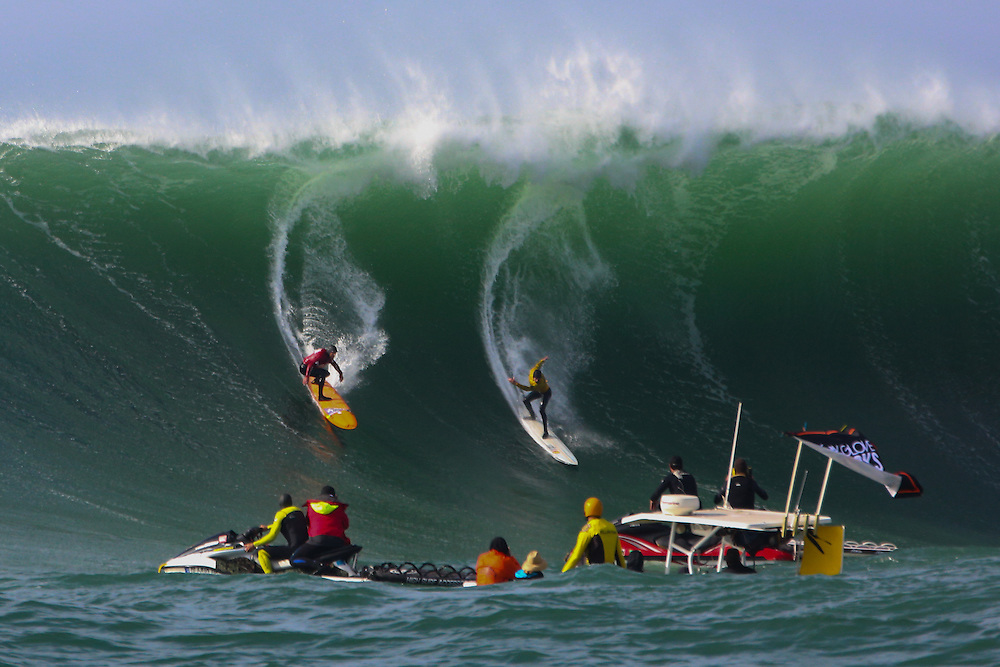 Tyler Fox (red jersey) and Grant Baker (yellow jersey) drop in on a wave during the final heats at Mavericks Surf Contest on January 24th,2014 off Pillar Point Harbor near Half Moon Bay,CA. Baker went on to win the competition.  (Charles Hall/challphotos.com)