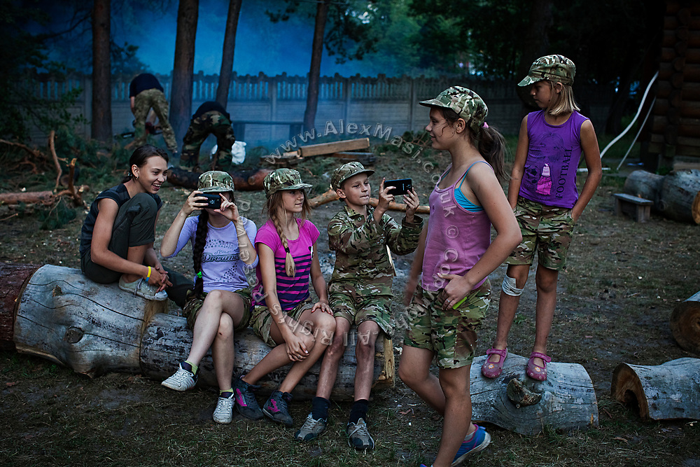 Youngsters participating to the ultra-nationalistic Azovets children's camp are taking pictures with their phones during a daily 30-minute break during which they are allowed to speak with parents and relax near the village of Buzova, 30 km west of Kiev, the capital of Ukraine.