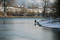 Peaceful scene of a man fishing in the wintry Reuss river in Switzerland.