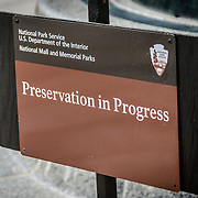 "Preservation in Progress Sign. A National Park Service ""Preservation in Progress"" sign at the site of repairs at the National World War II Memorial on the National Mall in Washington DC as at July 2, 2012."