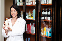 Happy beauty salon employee looking away while holding cosmetic products