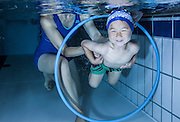 Young boy underwater with his mum helping him through a hoop
