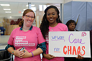 "Westbury, New York, USA. January 15, 2017. L-R, KARLA BRADLEY, of Hempstead, and NIA ADAMS, of Hempstead, are wearing pink ""I Stand with Planned Parenthood"" T-shirts and Adams holds sign ""We want Care not CHAOS"" at the ""Our First Stand"" Rally against Republicans repealing the Affordable Care Act, ACA, taking millions of people off health insurance, making massive cuts to Medicaid, and defunding Planned Parenthood. Hosts were Reps. K. Rice (Democrat - 4th Congressional District) and T. Suozzi (Dem. - 3rd Congress. Dist.)."