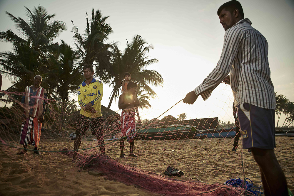 A group of fishermen undo their nets after making it back to the shore of Rathgama beach after a morning of fishing. Years ago, beach pollution was a pressing issue that affected beaches such as Rathgama, but with the solid waste management campaigns initiated by Arthavida Intermediary Limited in 2000 with the support of Australian Aid, communities were mobilized to clean and protect these idyllic beaches. 17 years onwards, everyone from fishermen to surfers can enjoy the views and waters of a pristine, unpolluted stretch of beach. © Reza Akram / DFAT 2017