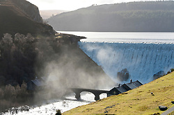 © Licensed to London News Pictures. 11/02/2019. Elan Village, Powys, UK. Water rages over the Caban-coch dam as Caban-coch reservoir reached it's 35,500 megalitre capacity at Elan Valley village near Rhayader in Powys, Wales, UK. After a summer of drought. recent torrential rain in Powys has mostly filled the complex of Elan valley reservoirs and taken river levels to the tops of river banks in Powys, Wales, UK. Elan Valley dams supply Birmingham in the West Midlands UK with water via a gravity feed. Photo credit: Photographers name/LNP