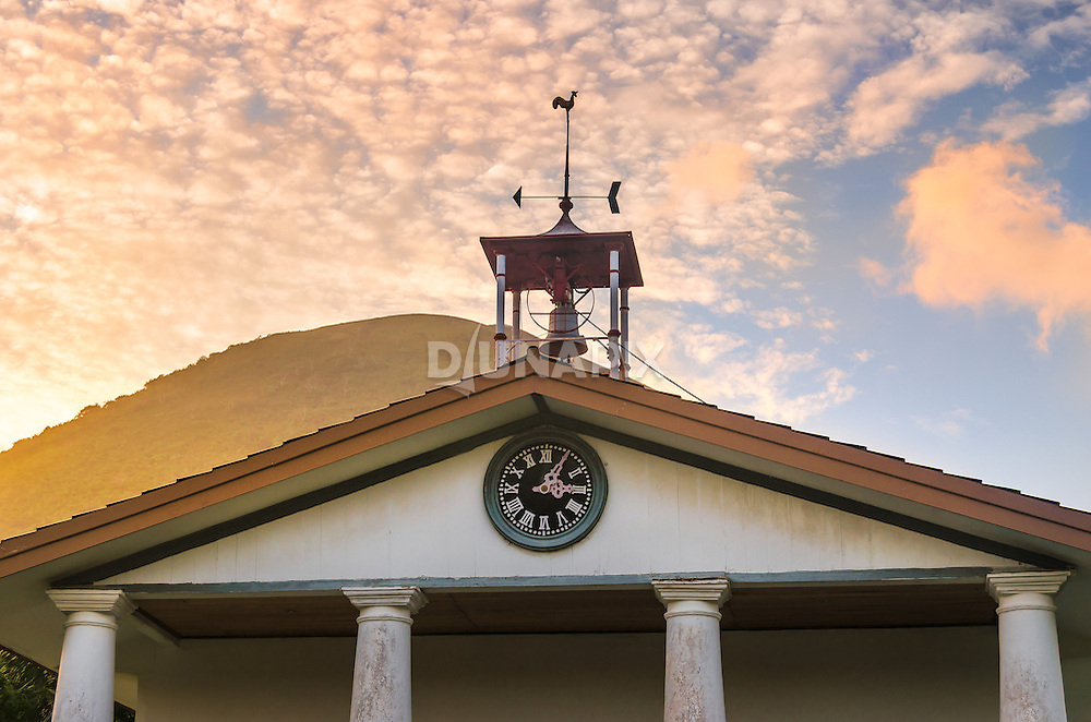 The old Dutch church of Banda Neira dates to 1852. The bronze church bell is believed to be one the oldest still in use. Behind the church, the sun sinks behing Gunung Api volcano.