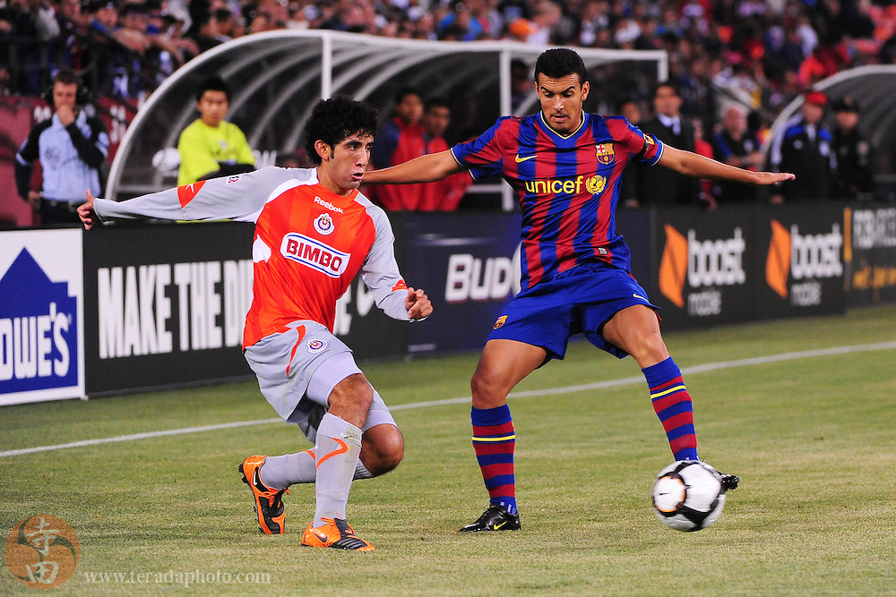 August 8, 2009; San Francisco, CA, USA; Chivas de Guadalajara defender Edgar Mejia (20) passes the ball against FC Barcelona defender Pedro Rodriguez (27, right) during the first half in the Night of Champions international friendly contest at Candlestick Park.