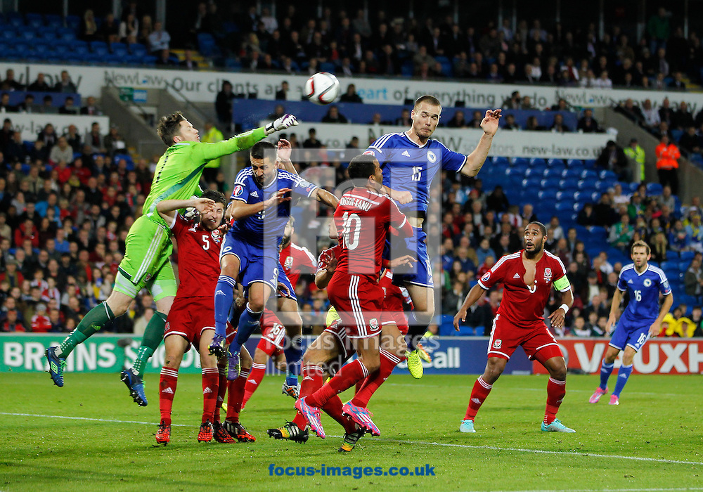 Wayne Hennessey of Wales punches the ball clear against Bosnia and Herzegovina during the UEFA Euro 2016 Qualifying match at the Cardiff City Stadium, Cardiff<br /> Picture by Mike  Griffiths/Focus Images Ltd +44 7766 223933<br /> 10/10/2014