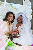Bride with mother showing her engagement ring at bridal shower