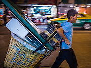 30 JUNE 2016 - BANGKOK, THAILAND: A vendor wheels his flower stall away after closing for the day at Pak Khlong Talat. Sidewalk vendors around Pak Khlong Talat, Bangkok's famous flower market, face eviction if they reopen on July 1. As a part of the military government sponsored initiative to clean up Bangkok, city officials have been trying to shut down the sidewalk vendors around the flower market. The vendors were supposed to be gone by the end of March, but city officials relented at the last minute with a compromise allowing vendors to stay until June 30. When vendors dismantled their booths after business on June 30, they weren't sure if they will be allowed to reopen July 1. Some vendors have moved to new locations approved by the government but many have not because they can't afford the higher rents in the new locations.     PHOTO BY JACK KURTZ