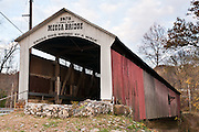 "Mecca Covered Bridge (150 feet long) was built in Burr Arch style over Big Raccoon Creek in 1873 by J.J. Daniels in historic Parke County, Indiana, USA. Red and white paint protects the wood. The traditional ""Cross this bridge at a walk"" sign required slow vehicle speed, but traffic is now diverted to an adjacent modern bridge."
