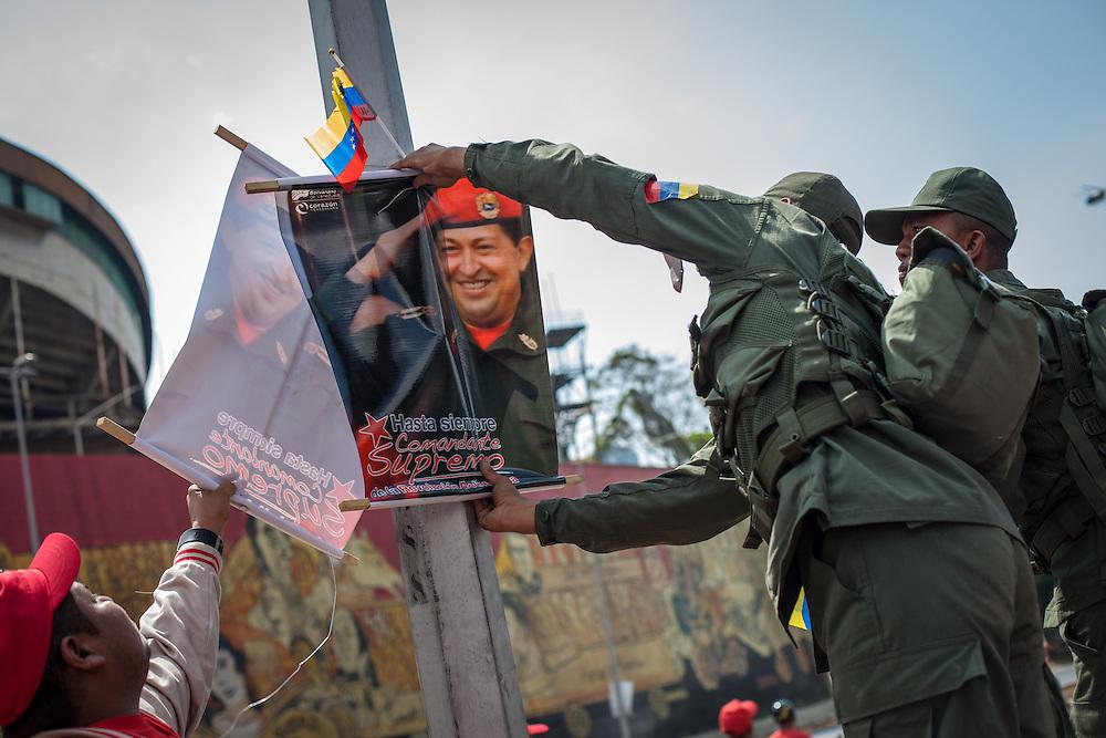 Soldados de la República Bolivariana de Venezuela toman un afiche de Hugo Chávez durante el traslado fúnebre hacia el 23 de Enero. Caracas, 15 Marzo, 2013 (Foto / Ivan Gonzalez)