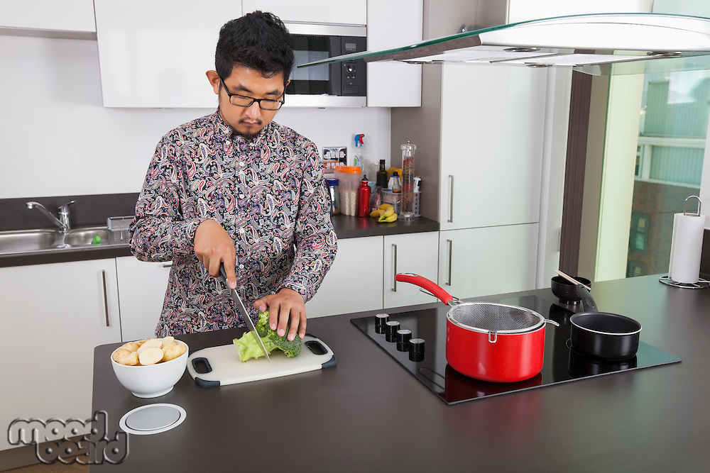 Young man chopping broccoli at kitchen counter
