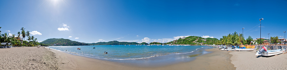 Beach with fishing boats on Playa Principal in Zihuatanejo, Mexico. High resolution panorama.