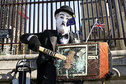 © Licensed to London News Pictures. 22/10/2019. London, UK. A protester dressed as Charlie Chaplin is seen smashing a TV screen with a hammer with 'Brexit' written on it, outside The Houses of Parliament as MPs begin scrutinising the Brexit Bill in the House of Commons. Photo credit: Dinendra Haria/LNP