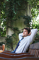 Businessman sitting on park bench relaxing