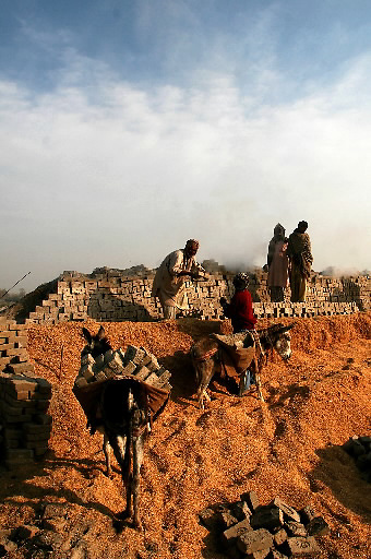 Pakistani men work at a brickyard in Khairo Dero village, in Larkana, Pakistan, on Thursday, Jan. 24, 2008. Pakistan is seeking to sustain growth in a country where the government estimates a fourth of the population lives in poverty, or on less than a dollar a day.