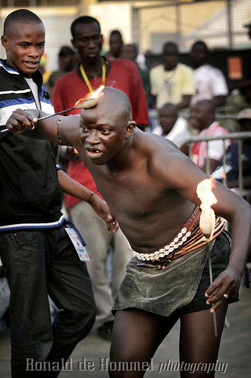 Superstition plays a big role in African traditional wrestling. During the international championship of The Economic Community Of West African States (ECOWAS or CEDEAO) in Dakar Senegalese fighters prepare by covering their bodies in solutions prepared by the Marabout, a medicine man. They also wear small amulets and shells or play with fire. ..After losing the title to Nigeria last year, the Senegalese home team came out as champion again this time. The championship is prestigious, but commercial wrestling where the fighters are allowed to punch (lutte avec frappe) is more popular with audience and players. The prize money in those fights goes up to 150.000 Euros. The matches attract up to 60.000 spectators. Wrestling has become more popular than football in Senegal in recent years.