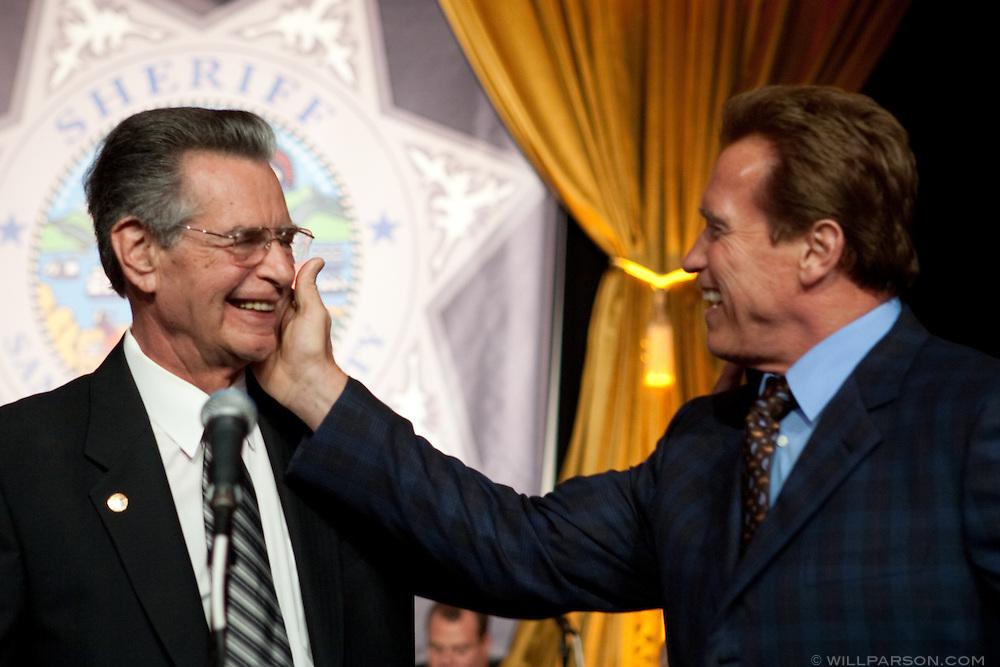 California Governor Arnold Schwarzenegger touches the cheek of San Diego Sheriff Bill Kolender at Kolender's retirement party, Oct. 05, 2009.